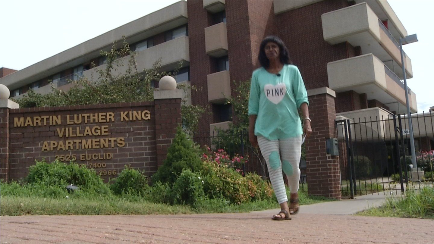 Virginia Dale walks past the sign for Martin Luther King Apartments. (KCTV5)