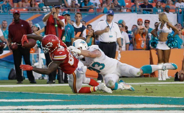 Kansas City Chiefs running back Joe McKnight (22) stretches for a touchdown as Miami Dolphins outside linebacker Jason Trusnik (93) defends during the second half of an NFL football game, Sunday, Sept. 21, 2014, in Miami Gardens, Fla. (AP)