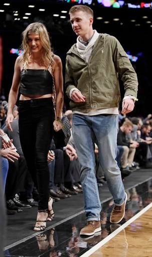 (AP Photo/Frank Franklin II). Genie Bouchard, walks the court with her blind date, John Goehrke, right, during the first half of an NBA basketball game between the Brooklyn Nets and the Milwaukee Bucks Wednesday, Feb. 15, 2017, in New York.