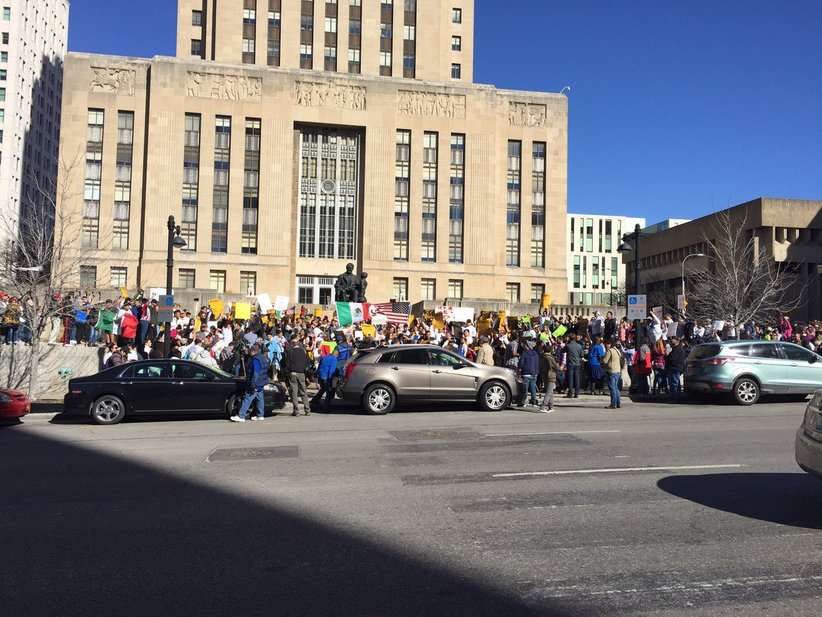 "About 500 protesters gathered near City Hall, many holding banners and signs such as ""Somos America,"" which translates to ""We're America."" (Caroline Sweeney/KCTV5 News)"