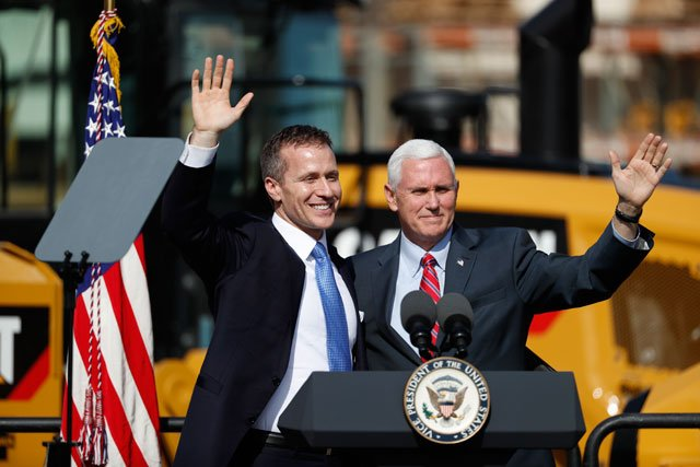 Vice President Mike Pence waves as he is introduced by Missouri Gov. Eric Greitens, left, before delivers remarks at Fabick Cat, a family-owned equipment and engine dealer, Wednesday, Feb. 22, 2017, in Fenton, Mo. (AP Photo/Jeff Roberson)