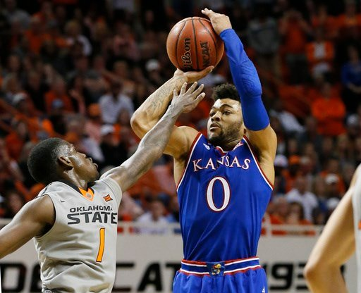 Kansas guard Frank Mason III (0) shoots over Oklahoma State guard Jawun Evans (1) in the second half of an NCAA college basketball game in Stillwater, Okla., Saturday, March 4, 2017. Kansas won 90-85. (AP Photo/Sue Ogrocki)