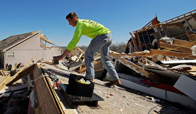 Brent Benson salvages items from a friend's destroyed home Tuesday, March 7, 2017, after a tornado tore through Oak Grove, Mo., Monday night. (AP Photo/Charlie Riedel)
