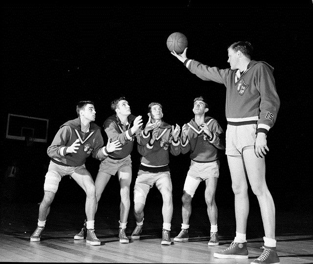 """Clyde Lovellette, 6'9"""" center for the Kansas University basketball team, right, holds the ball aloft while teammates angle for position, left to right: Bill Lienhard, Bill Hougland, Bob Kenney, Jerry Waugh, and Lovellette. (AP Photo/Anthony Camerano)"""