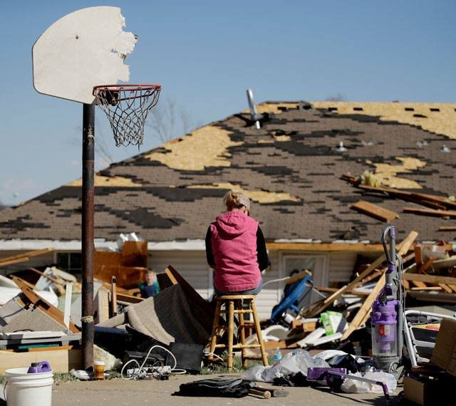 Cori Brown takes a break from helping salvage items from a friend's tornado-damaged home Tuesday, March 7, 2017, after a severe storm passed through Oak Grove, Mo. Monday night. (AP Photo/Charlie Riedel)