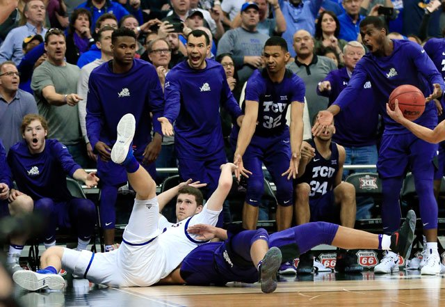 Kansas guard Sviatoslav Mykhailiuk, bottom left, lands on and fouls TCU guard Desmond Bane (1) during second half of an NCAA college basketball game in the quarterfinal round of the Big 12 tournament in Kansas City, Mo., Thursday, March 9, 2017. (AP)