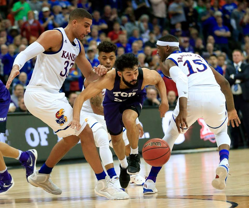 TCU guard Alex Robinson (25) splits Kansas defenders Landen Lucas (33) and Carlton Bragg Jr. (15) during second half of an NCAA college basketball game in the quarterfinal round of the Big 12 tournament in Kansas City, Mo., Thursday, March 9, 2017. (AP)
