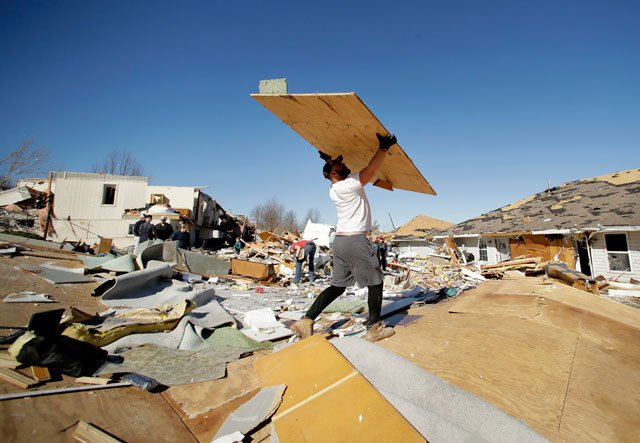 Bryant Carter removes debris as he helps salvages items from a friend's tornado-damaged home Tuesday, March 7, 2017, after a severe storm passed through Oak Grove, Mo. Monday night. (AP Photo/Charlie Riedel)