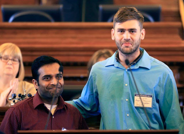 Alok Madasani, left, and Ian Grillot, right, embrace and smile after they were honored by the Kansas House of Representatives in Topeka, Kan., Thursday, March 16, 2017 (AP Photo/Orlin Wagner)