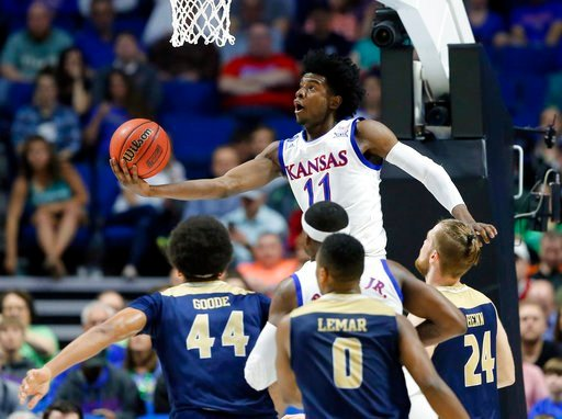 Kansas' Josh Jackson (11) goes up for a shot over UC Davis' Garrison Goode (44), Brynton Lemar (0) and Mikey Henn (24) in the first half of a first-round game in the men's NCAA college basketball tournament in Tulsa, Okla., Friday March 17, 2017. (AP)