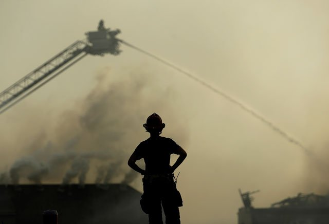 A firefighter watches from the scene of an apartment complex fire as firefighters douse fires at nearby homes Monday in Overland Park, Kan. (AP Photo/Charlie Riedel)