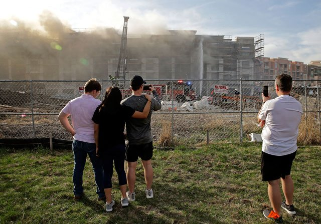 People watch an eight-alarm fire that began at an apartment complex under construction and than spread to several nearby homes Monday in Overland Park. (AP Photo/Charlie Riedel)