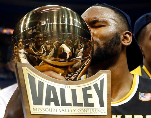 (AP Photo/Jeff Roberson). FILE - In this March 5, 2017, file photo, Wichita State's Shaquille Morris kisses the trophy after defeating Illinois State 71-51 in an NCAA basketball game to win the championship of the Missouri Valley Conference.
