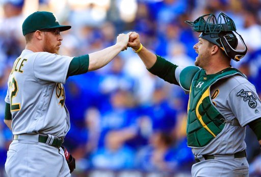Oakland Athletics relief pitcher Sean Doolittle, left, is congratulated by catcher Stephen Vogt, right, following a baseball game against the Kansas City Royals at Kauffman Stadium in Kansas City. (AP)
