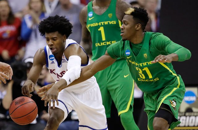 Kansas guard Josh Jackson, left, and Oregon guard Dylan Ennis reach for the ball during the second half of the Midwest Regional final of the NCAA men's college basketball tournament, Saturday, March 25, 2017, in Kansas City, Mo. (AP Photo/Charlie Riedel)