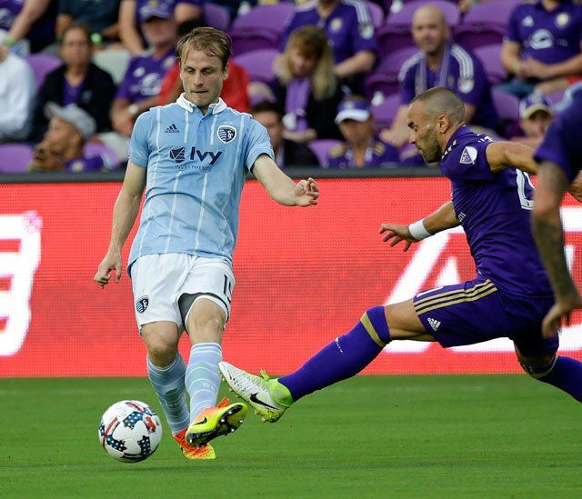 Sporting Kansas City's Seth Sinovic, left, moves the ball past Orlando City's Scott Sutter during the first half of an MLS soccer game, Saturday, May 13, 2017, in Orlando, Fla. (AP Photo/John Raoux)