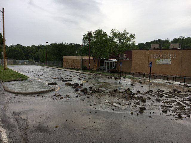 The break has caused the community center's parking lot to flood and water to flow into the road. (KCTV5)