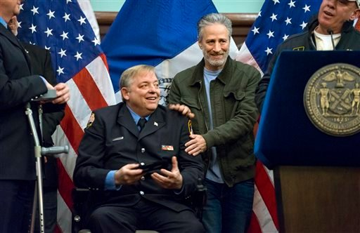 Comedian Jon Stewart, right, speaks during a ceremony just before retired FDNY firefighter and Sept. 11 first responder Ray Pfeifer, front left, was given a key to the city at New York's City Hall on Saturday, Jan. 9, 2016.  (AP)