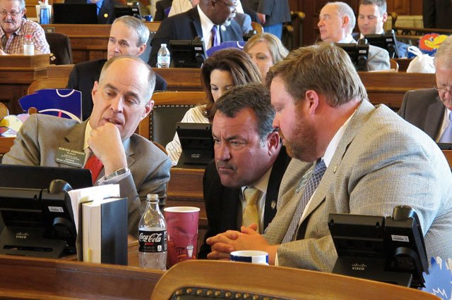 Kansas House Taxation Committee Chairman Steven Johnson, left, R-Assaria, confers with Reps. Kent Thompson, R-Iola, and Blaine Finch, right, R-Ottawa, during the House's session Wednesday at the Statehouse in Topeka. (AP Photo/John Hanna)
