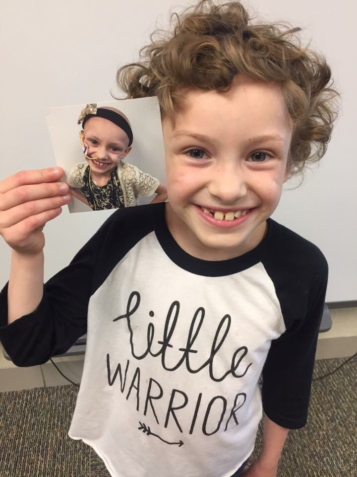 Sophi Eber at the end of the school year holding a photo of herself from the first day of 1st grade.
