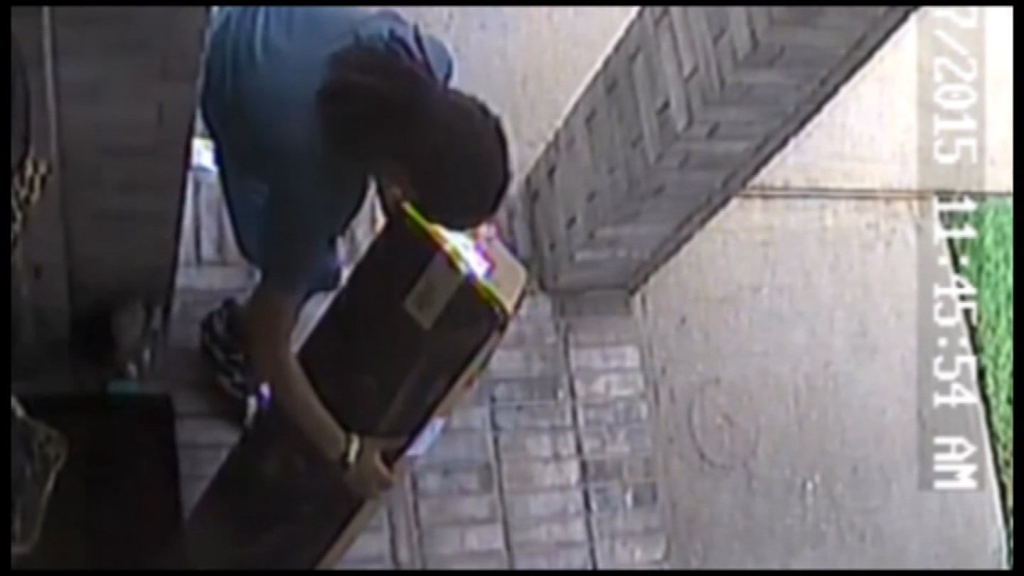 Surveillance camera view of a thief checking out a package obviously not addressed to him. (CBS NEWS)
