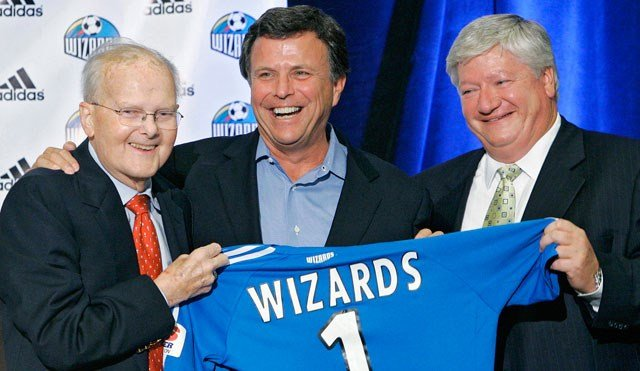Lamar Hunt, left, Neal Patterson, center, and Clif Illig hold up a Wizards jersey during a press conference announcing the sale of the Kansas City Wizards at the Overland Park Convention Center, Aug. 31, 2006. (AP Photo/The Kansas City Star, John Sleezer)