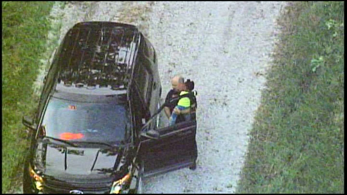 A police officer hugs a missing 3-year-old girl after she was discovered in Leavenworth County. (Chopper5)
