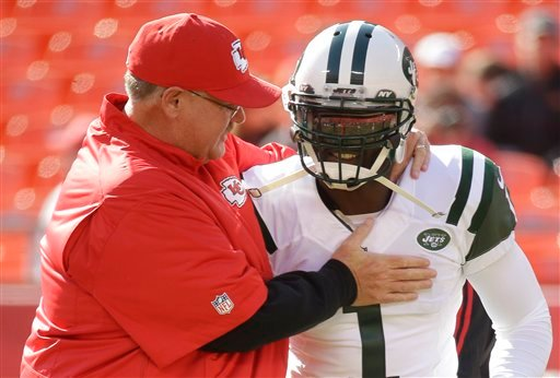 Kansas City Chiefs head coach Andy Reid meets with New York Jets quarterback Michael Vick (1) before an NFL football game in Kansas City, Mo., Sunday, Nov. 2, 2014. (AP Photo/Charlie Riedel)