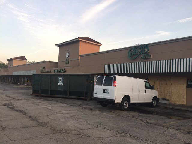 The bar and grill was forced to board up its doors and the wall that collapsed and to move its chairs and tables outside to let them dry. (KCTV5)