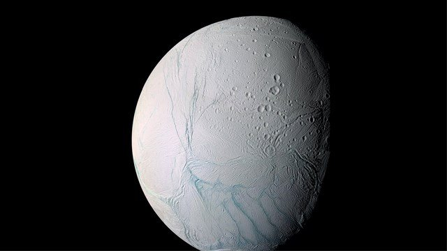 "An ocean at least as large as Lake Superior lies below a thick layer of ice on Enceladus, a moon of Saturn. Long ""tiger stripe"" fractures appear in this picture of Enceladus. (File Photo)"