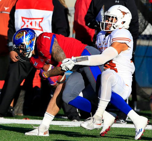 Kansas wide receiver LaQuvionte Gonzalez (1) is tackled by Texas safety Dylan Haines (14) during the first half of an NCAA college football game in Lawrence, Kan., Saturday, Nov. 19, 2016. (AP Photo/Orlin Wagner)