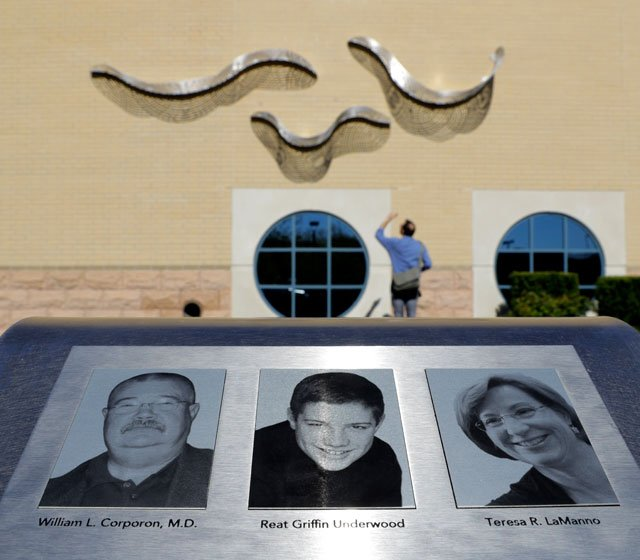 A man views a memorial to victims of an April 2014 shooting at the Jewish during it's dedication at the Jewish Community Center Tuesday, April 12, 2016, in Overland Park, Kan. (AP Photo/Charlie Riedel)