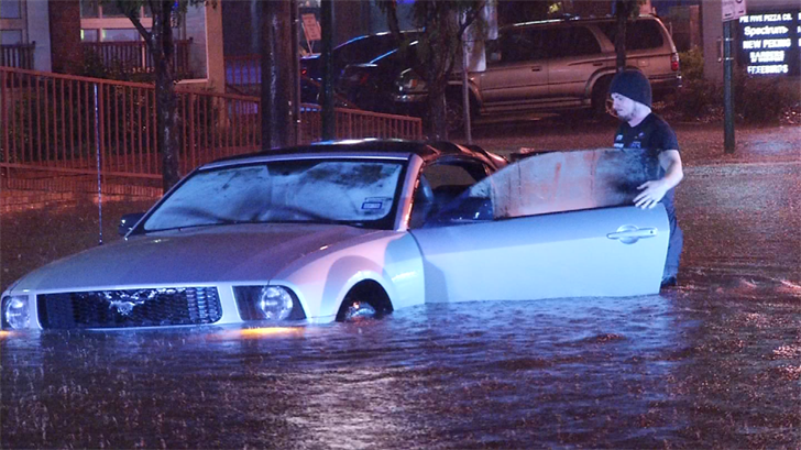 File photo -- A man's car is flooded in Westport during this summer's flooding. (KCTV)