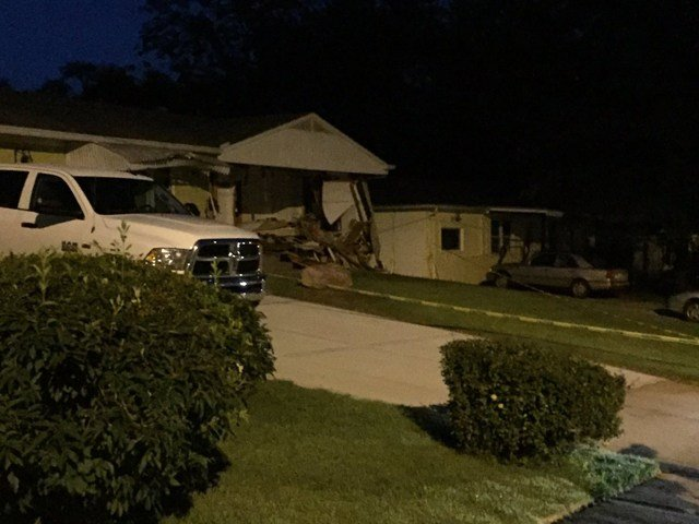 The car ripped a hole in the side of the house and left a street sign in the driveway. (KCTV5)