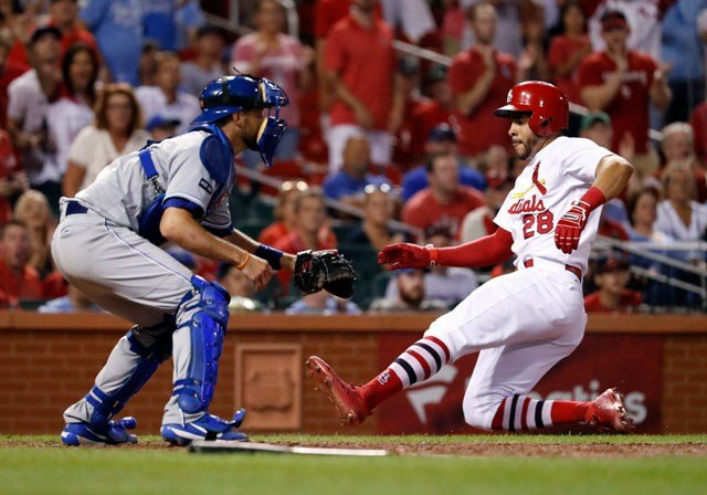 St. Louis Cardinals' Tommy Pham, right, scores past Kansas City Royals catcher Drew Butera during the eighth inning of a baseball game Thursday, Aug. 10, 2017, in St. Louis. (AP Photo/Jeff Roberson)