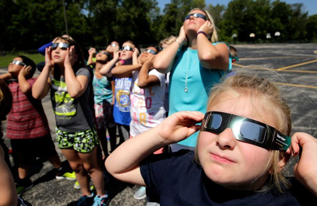 Fourth graders at Clardy Elementary School in Kansas City practice the proper use of their eclipse glasses in anticipation of Monday's solar eclipse. (AP Photo/Charlie Riedel)