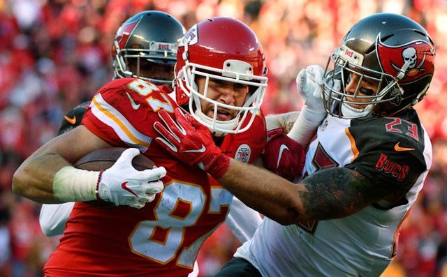 Kansas City Chiefs tight end Travis Kelce (87) breaks a tackle attempt by Tampa Bay Buccaneers safety Chris Conte (23) during the second half of an NFL football game in Kansas City, Mo., Sunday, Nov. 20, 2016. (AP Photo/Ed Zurga)