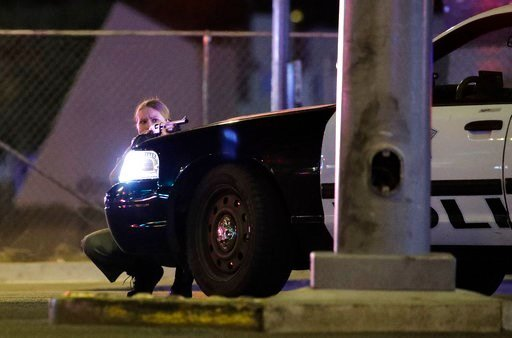 (AP Photo/John Locher). A police officer takes cover behind a police vehicle during a shooting near the Mandalay Bay resort and casino on the Las Vegas Strip, Sunday, Oct. 1, 2017, in Las Vegas.