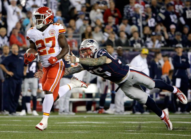 Kansas City Chiefs running back Kareem Hunt (27) eludes New England Patriots defensive end Cassius Marsh (55) as he runs for a touchdown after catching a pass from Alex Smith on Sept. 7, 2017, in Foxborough, Mass. (AP Photo/Steven Senne)