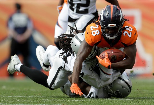 Denver Broncos running back Jamaal Charles is tackled by members of the Oakland Raiders defense during the first half of an NFL football game Sunday, Oct. 1, 2017, in Denver. (AP Photo/Joe Mahoney)