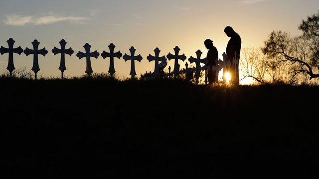 Kenneth and Irene Hernandez pay their respects as they visit a makeshift memorial with crosses placed near the scene of a shooting at the First Baptist Church of Sutherland Springs, Monday, Nov. 6, 2017, in Sutherland Springs, Texas. (AP Photo/Eric Gay)