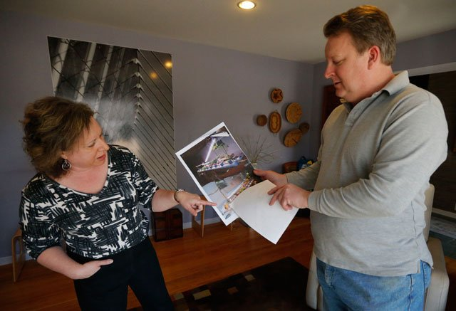 Addie and Bob Harte share photos from the day of a police raid on their home in Leawood, Friday, March 29, 2013. (AP Photo/Orlin Wagner)
