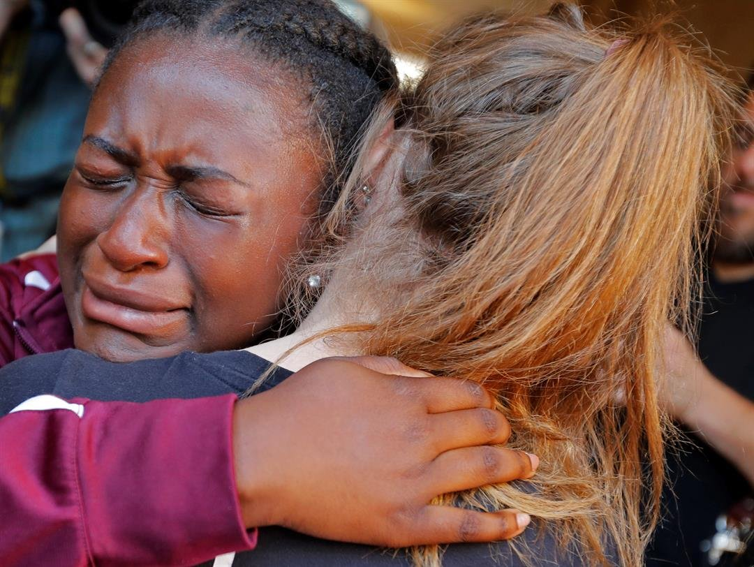 Marla Eveillard, 14, cries as she hugs friends before the start of a vigil at the Parkland Baptist Church, for the victims of Wednesday's shooting at the Marjory Stoneman Douglas High School in Parkland, Fla., Thursday, Feb. 15, 2018. (AP)