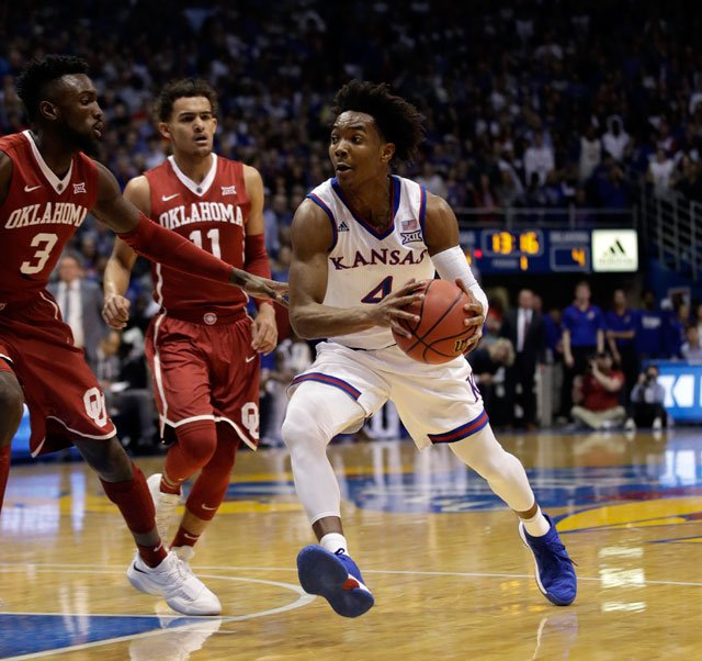 Kansas guard Devonte' Graham (4) and Oklahoma forward Khadeem Lattin (3) during the first half of an NCAA college basketball game in Lawrence, Kan., Monday, Feb. 19, 2018. (AP Photo/Orlin Wagner)