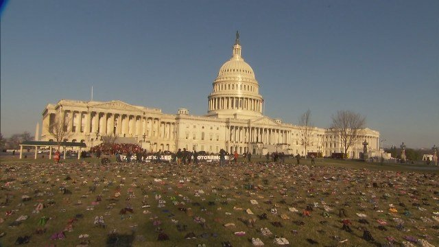 Volunteers placed 7,000 empty shoes on the Capitol grounds to represent the number of children fatally shot since Newtown, calling on Congress to take action. (CBS)