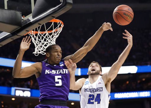 Kansas State's Barry Brown (5) blocks a shot by Creighton's Mitch Ballock (24) during the second half of a first-round game in the NCAA men's college basketball tournament in Charlotte, N.C., Friday, March 16, 2018. (AP Photo/Gerry Broome)