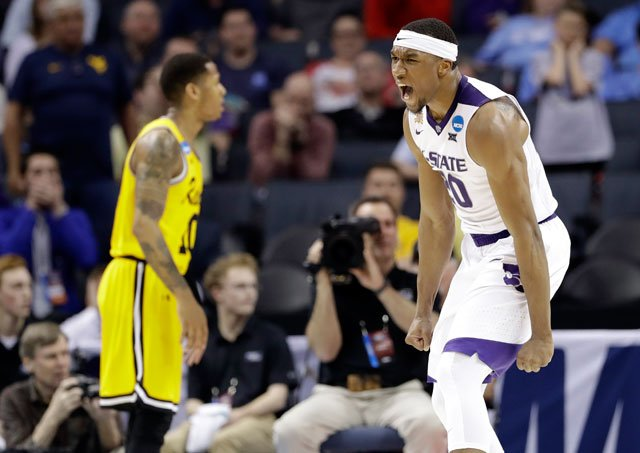 Kansas State's Xavier Sneed (20) celebrates after a dunk against UMBC during the second half of a second-round game in the NCAA men's college basketball tournament in Charlotte, N.C., Sunday, March 18, 2018. (AP Photo/Gerry Broome)