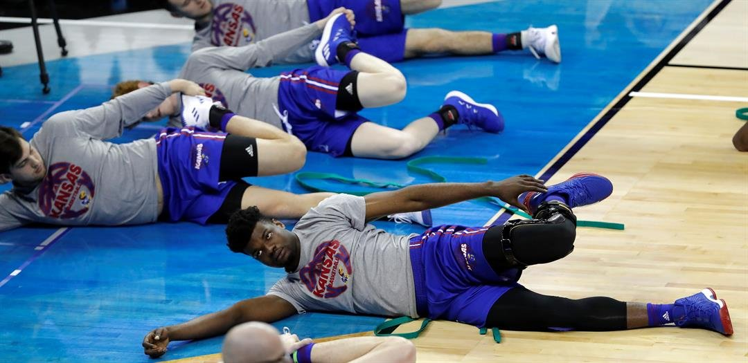 Kansas center Udoka Azubuike, right, stretches during practice at the NCAA men's college basketball tournament, Thursday, March 22, 2018, in Omaha, Neb. Kansas faces Clemson in a regional semifinal on Friday. (AP Photo/Charlie Neibergall)