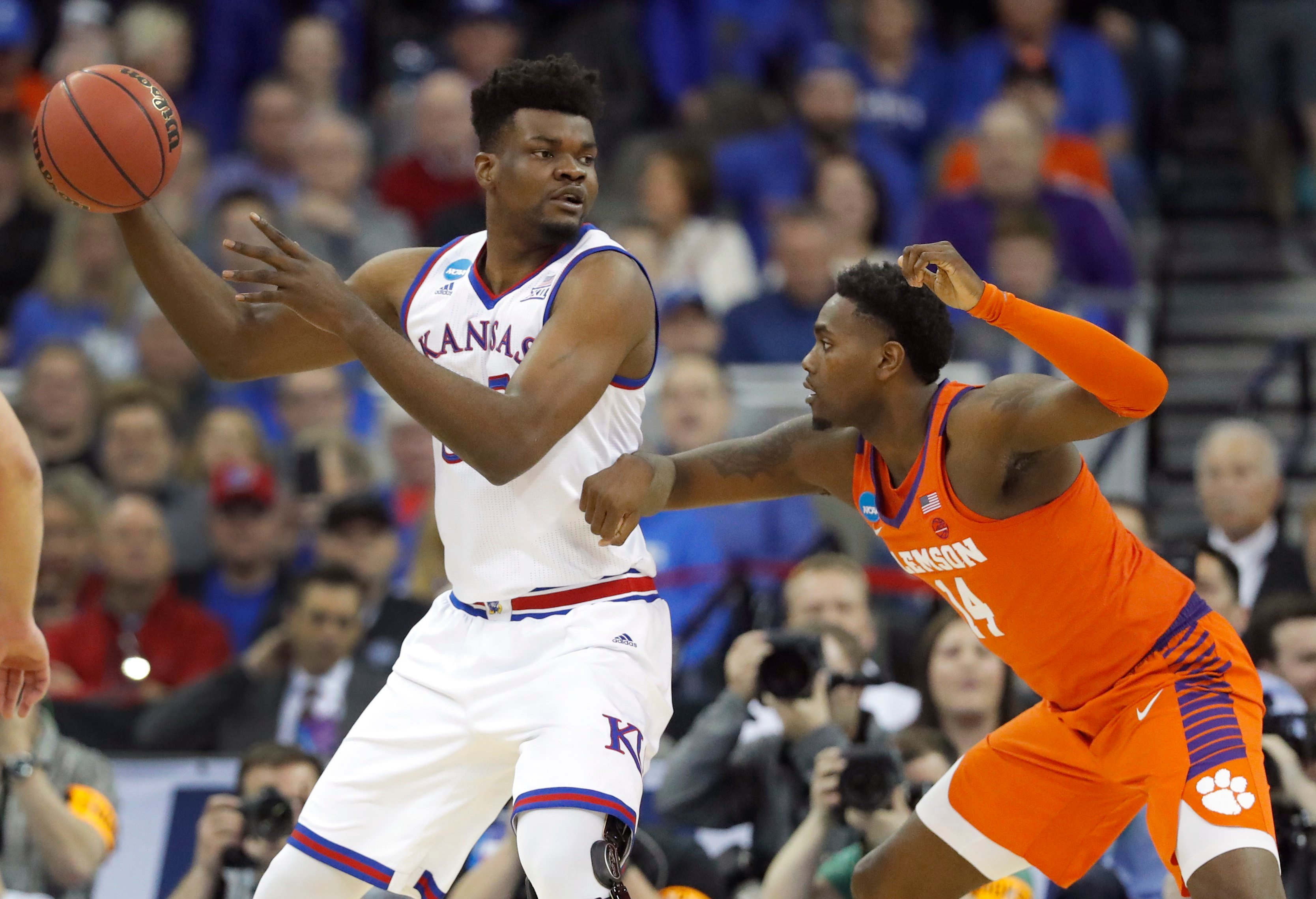 Kansas' Udoka Azubuike, left, looks to pass around Clemson's Elijah Thomas during the first half of a regional semifinal game in the NCAA men's college basketball tournament Friday, March 23, 2018, in Omaha, Neb. (AP Photo/Charlie Neibergall)