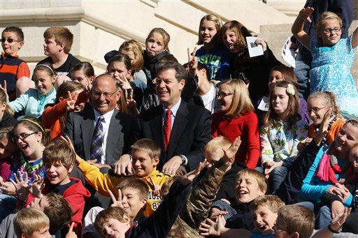 Schoolchildren from Sabetha clown around as they pose with former Gov. Brownback, center, with the red tie, on the steps of the Statehouse in Topeka in 2012. Sitting to Brownback's left is state Rep. Randy Garber of Sabetha. (AP Photo/John Milburn)